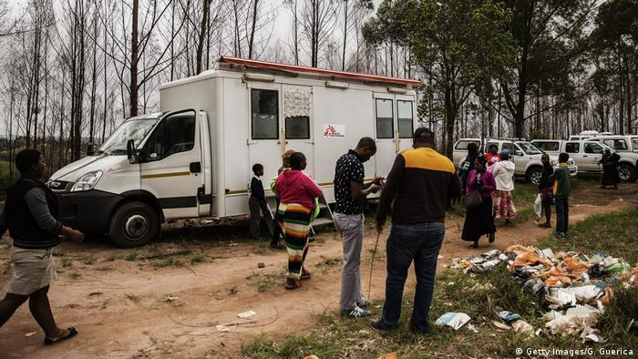 People walk past a mobile testing unit from MSF on the outskirts of Eshowe