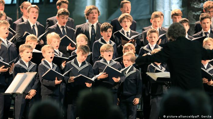 Choir boys singing in sailor suits