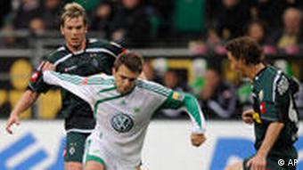 Wolfsburgs Zvjezdan Misimovic (Mitte) ist vor den beiden Mönchengladbachern Spielern Thorben Marx (links) und Roel Brouwers am Ball (AP Photo/Fabian Bimmer)