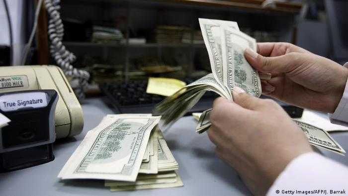 Foto simbólica de una persona que cuenta dólares en un banco