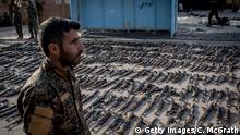 22.03.2019 AL MAYADIN, SYRIA - MARCH 22: An SDF (Syrian Democratic Forces) fighter looks over seized ISIL weapons that were found in the last stronghold of the extremist group as they were displayed at an SDF base on March 22, 2019 outside Al Mayadin, Syria. In recent days the U.S.-backed Syrian Democratic Forces have taken control of the ISIL encampment on the eastern bank of the Euphrates in Baghouz, the extremist groups last hold out. The SDF have combed the area in an attempt to flush out the last remaining ISIL fighters ahead of the much anticipated victory announcement and the end of the Islamic States caliphate (Photo by Chris McGrath/Getty Images)
