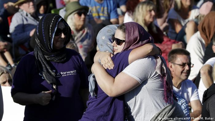 People embrace in a show of love during a vigil in Hagley Park following the March 15 mass shooting in Christchurch