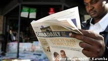 A newspaper consumer reads a copy of China's Africa edition of its daily newspaper infront of a news stand in the Kenyan capital on December 14, 2012. China today launched an African edition of its China Daily newspaper, the latest media venture by Beijing on the continent. The relationship between China and the African continent is one of the most significant relationships in the world today, publisher and editor-in-chief of the state-run paper Zhu Ling wrote in the inaugural copy. AFP PHOTO/Tony KARUMBA (Photo credit should read TONY KARUMBA/AFP/Getty Images)