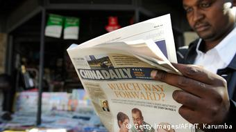 A man in Kenya reads a copy of China Daily's Africa edition