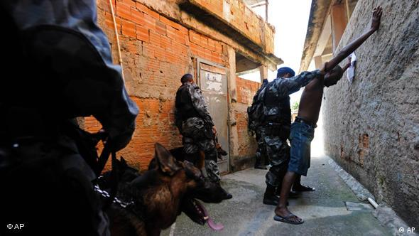 Police frisk a man as they search for drugs and weapons in the Morro do Adeus slum in Rio de Janeiro, Brazil, Sunday, Oct. 18, 2009. Brazilian officials are insisting security won't be a problem for the 2016 Olympics, despite drug-gang violence that plunged Rio into a day of chaos just two weeks after it was picked to host the games, when an hour-long firefight between rival gangs in one of the city's slums killed at least 12 people, injured six and saw a police helicopter shot down and eight buses set on fire Saturday. (AP Photo/Felipe Dana)