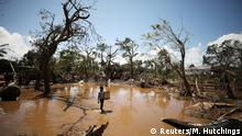 A child walks past debris as flood waters begin to recede in the aftermath of Cyclone Idai, in Buzi near Beira, Mozambique March 24, 2019. REUTERS/Mike Hutchings