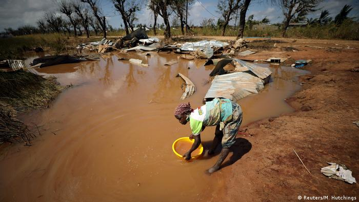 A woman collects water for washing as floodwaters begin to recede in the aftermath of Cyclone Idai, in Buzi near Beira
