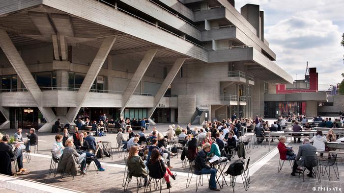 Menschen sitzen im Café vor dem Nationaltheater in London