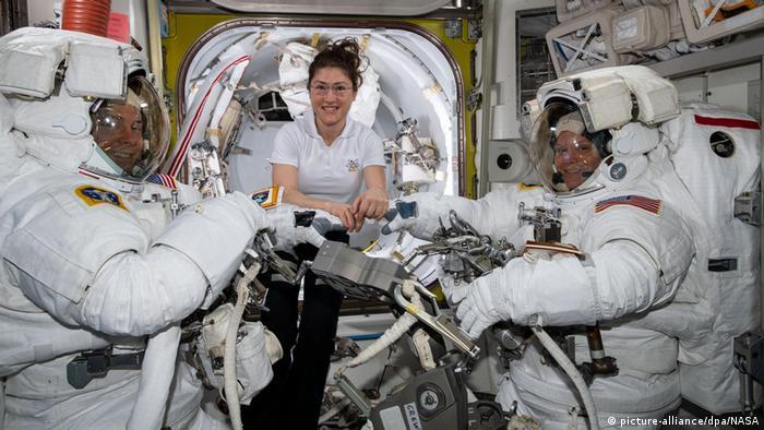 A astronauta da NASA Christina Koch, no meio, dá apoio a Nick Hague, à esquerda, e a Anne McClain, à direita, em seus trajes espaciais, pouco antes do início de uma caminha da espacial