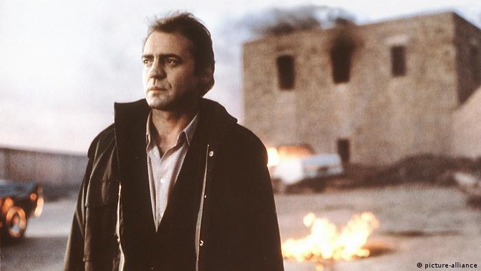 Ein Mann steht vor einem Haus aus dem Rauch aufsteigt. Im Hintergrund sind Flammen zu sehen (picture-alliance)