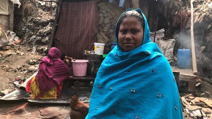 Eine Frau in einem blauen Schultertuch steht vor einer Müllhalde in Indien