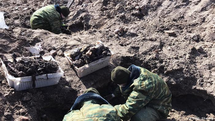 Soldiers from Belarussian special search batallion dig out the remains of Jews killed by the Nazis in Brest during WWII