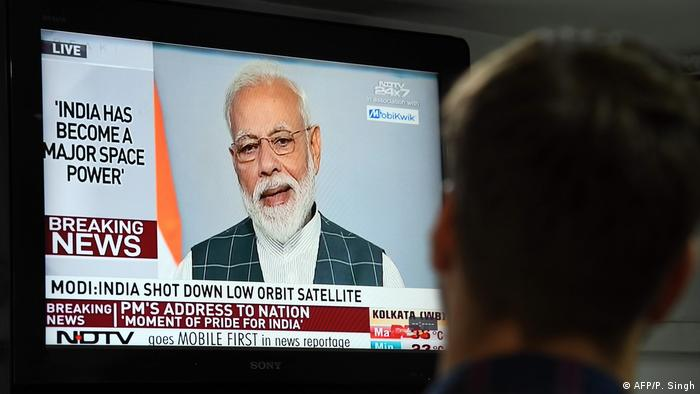 Indian Prime Minister Narendra Modi can be seen on a TV screen talking after India shot down a satellite as part of defense system tests