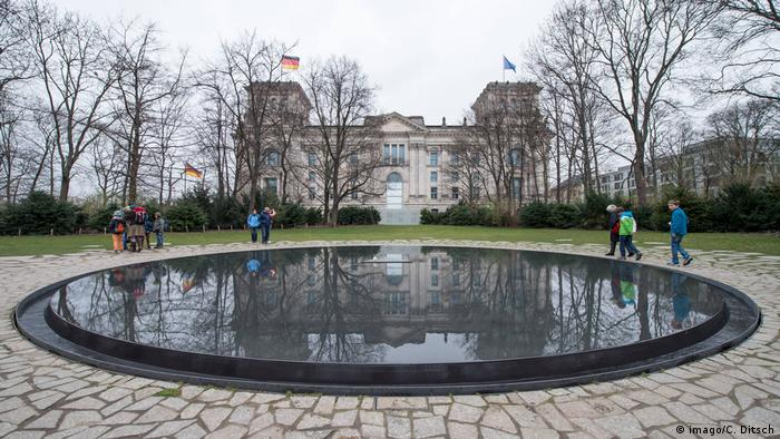 Kreisrundes Wasserbecken, im Hintergrund das Reichstagsgebäude, Denkmal für die im Nationalsozialismus ermordeten Sinti und Roma Europas, Berlin (imago/C. Ditsch)