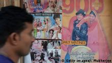 TO GO WITH India-entertainment-Bollywood-cinema,FOCUS by Aditya PHATAK In this photograph taken on December 5, 2014, an Indian cinemagoer walks past a poster of a screening of the popular Bollywood Hindi film 'Dilwale Dulhania Le Jayenge' (The Brave hearted Will Take The Bride Away) at the Maratha Mandir movie theatre in Mumbai. The 1995 Bollywood love flick titled Dilwale Dulhaniya Le Jayenge (The Brave Hearted Will Take Away the Bride) is now the longest running movie in Indian cinema history. DDLJ, as the movie is commonly known in India, is set to clock a successful run of 1000 weeks on December 12. AFP PHOTO / INDRANIL MUKHERJEE (Photo credit should read INDRANIL MUKHERJEE/AFP/Getty Images)