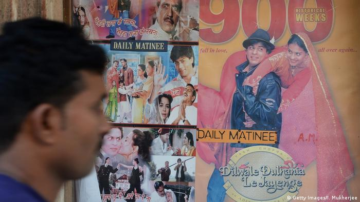 An Indian man walks past a poster of a popular Bollywood film