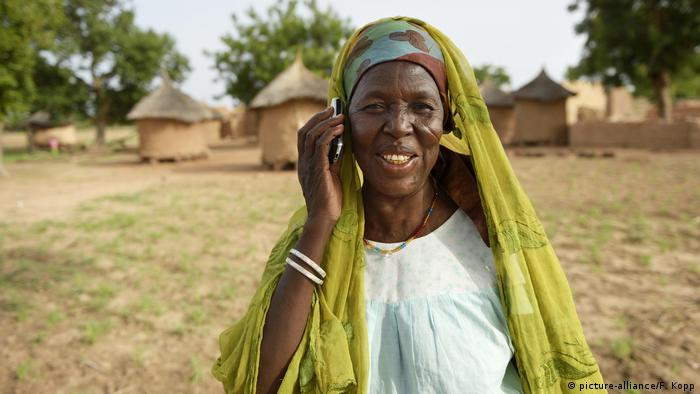 A woman holding a mobile phone in Burkina Faso, Africa. Photo credit: picture-alliance/F. Kopp.