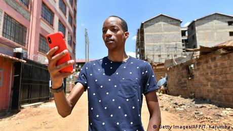 A man holds and looks at a red smartphone in a street in Nairobi (Getty Images/AFP/T. Karumba)