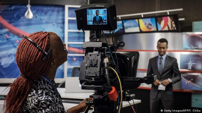 Eine Kamerafrau blickt auf den Monitor, im Hintergrund ein Moderator
