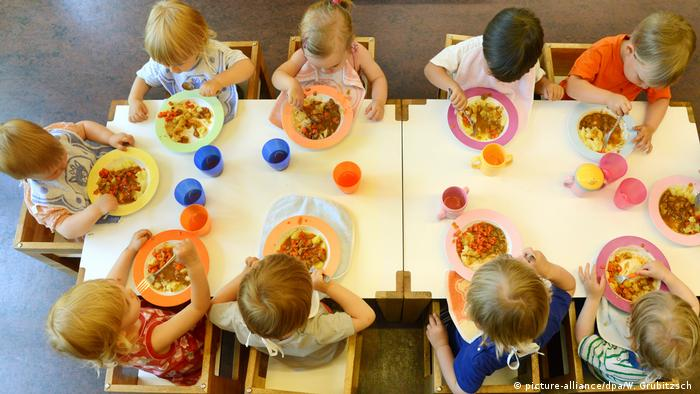 Children sit at a table in a day care and eat lunch
