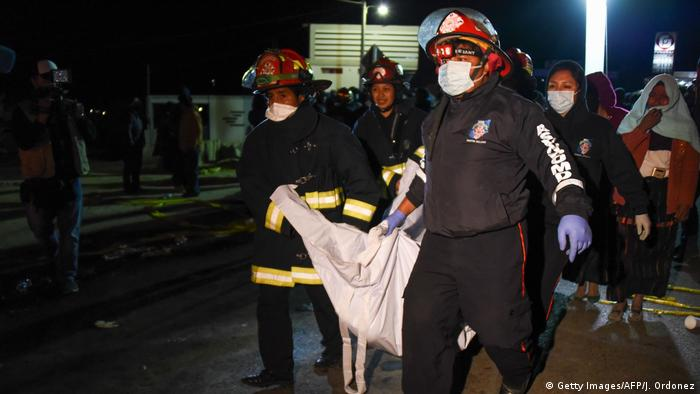 Firefighters carry the body of one of eighteen victims killed