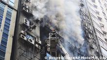 A firefighter works to douse a fire in a multi-storied office building in Dhaka, Bangladesh, Thursday, March 28, 2019. Fire Department control room official Ershad Hossain said by phone the FR Tower in Dhaka's Banani commercial district caught fire Thursday afternoon and at least 19 fire fighting units joined the operation to douse the blaze and rescue the people trapped inside. (AP Photo/Mahmud Hossain Opu )  