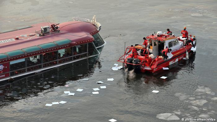 Firefighting officials throw oil absorbents into the Han River in Seoul, South Korea, (photo: picture-alliance/dpa)