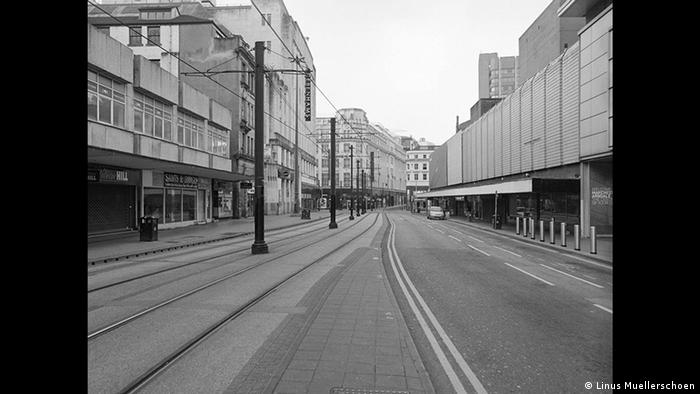 Seemingly black and white photo of an empty street with tram tracks in the middle and a single car parked in the distance (Copyright: Linus Muellerschoen)