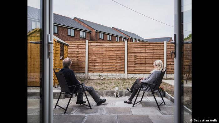 A man and a woman sitt in garden chairs on a patio in a yard walled off by a fence with tenement hosues in the background (Copyright: Sebastian Wells)
