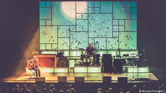 Gitarrist Diederik spielt und singt Blackbird, auf der Leinwand im Hintergrund ein Vogelschwarm, am Schlagzeug sitzt Bandleader Fred Gehring und singt mit