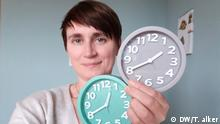 Author Tamsin Walker takes a selfie while holding up two clock faces with different times
