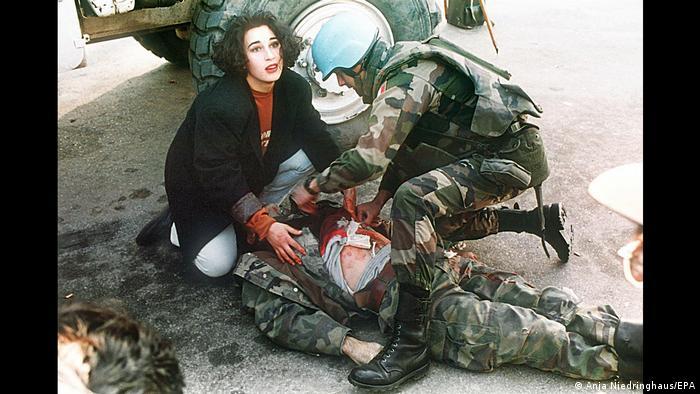 اگر از آنچه در مناطق جنگی رخ میدهد عکس نگیرم، کسی هم از آن آگاه نخواهد شد. اینها واژههای آنیا نیدرینگهاوس، عکاس جنگی آلمانی است که با نخستین گزارش تصویریاش از جنگ بالکان، افکار عمومی را به تعمق واداشت. عکس بالا یک سرباز آسیب دیده بوسنی را نشان میدهد که یک زن عابر پیاده به همراهی یک سرباز نیروهای سازمان ملل مشغول رساندن کمکهای اولیه به او هستند. این سرباز اندکی بعد همانجا جان داد.