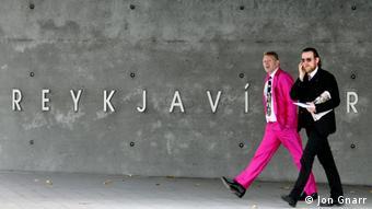 Йон Гнарр шагает с коллегой на фоне надписи Рейкьявик