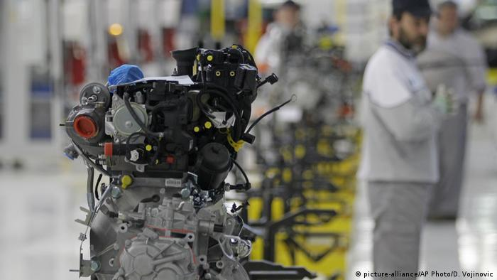 A factory worker looking at an engine of a Fiat 500 L car in the assembly hall in a Fiat factory in Serbia