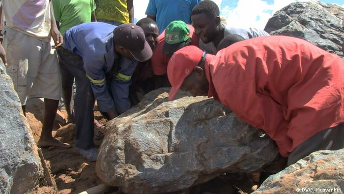 Five men are trying to heave a boulder away.
