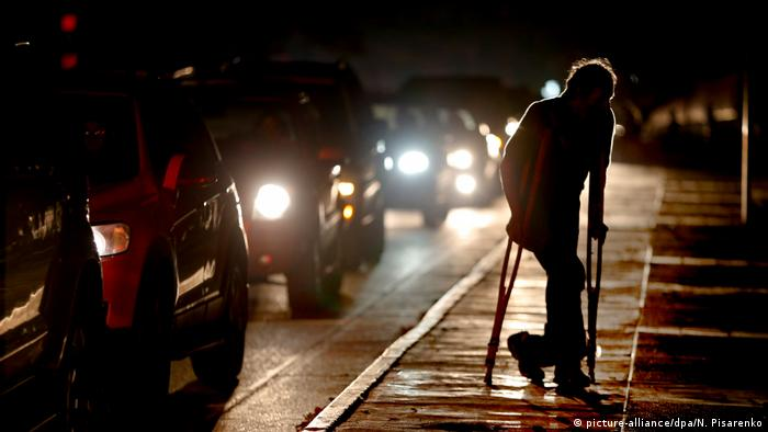 A man on crutches walks along a footpath at night (picture-alliance/dpa/N. Pisarenko)
