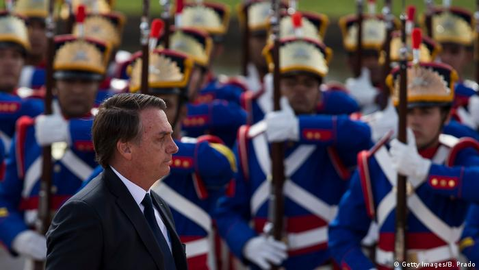 Presidente Jair Bolsonaro, de terno, caminha sobre tropa, que veste trajes especiais,
