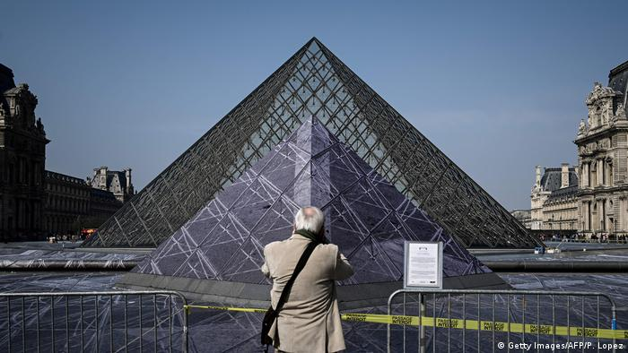 Man takes photo in front of Louvre pyramid