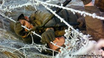 GDR soldiers on the ground, trying to get through a barbed-wire fence