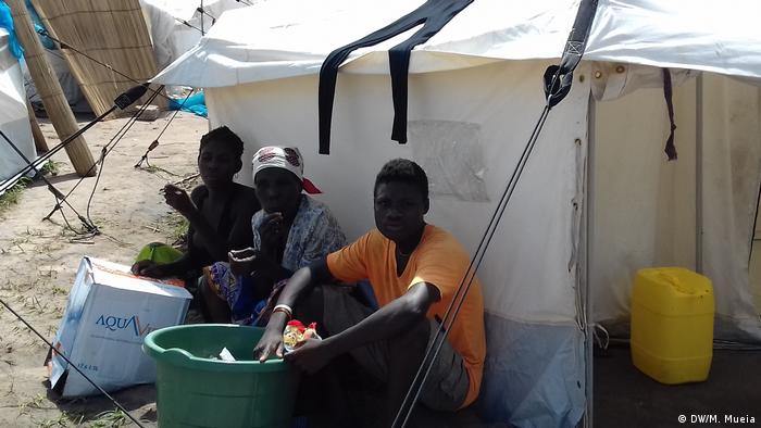 Three people sit outside a tent with a plastic bucket containing rations (DW/M. Mueia)