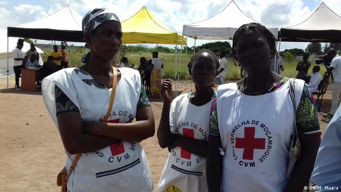 Three health workers wearking Red Cross vest stand outside (DW/M. Mueia)