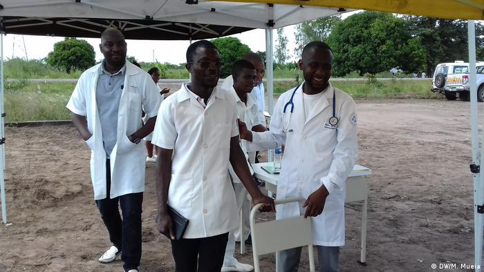 Doctors in white coats stand under a covered area (DW/M. Mueia)