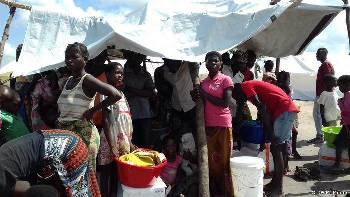 People stand in front of a makeshift shelter (DW/M. Mueia)