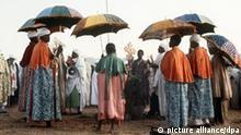 Gläubige und Geistliche während einer Weihe von Taufwasser beim Timkatfest der äthiopischen Christen in Lalibela. Sonnenschirme schützen die Gläubigen vor der sengenden Sonne.
