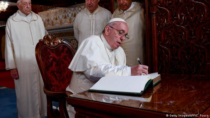 Pope Francis writes a message in the guest book of the mausoleum of Mohammed V in Rabat