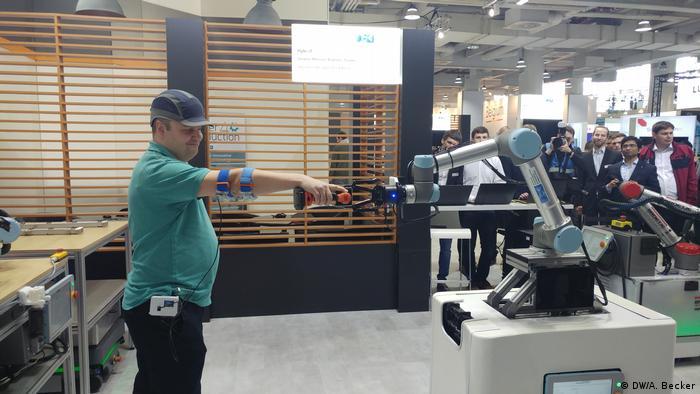 Man testing an AI robot at Hanover industrial fair