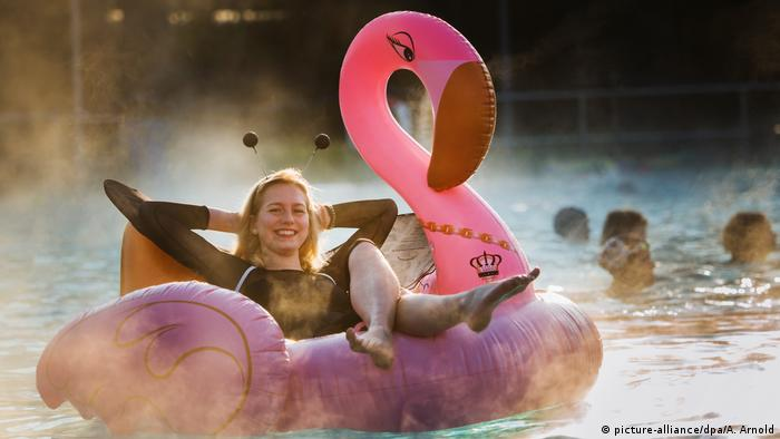 A girl floating on a pink flamingo inflatable toy (picture-alliance/dpa/A. Arnold)