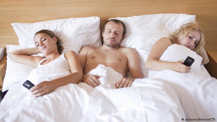Mann mit zwei Frauen in einem Hotelbett (picture-alliance/CTK)