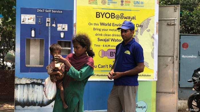 Drei Menschen vor einem Wasser ATM stehen