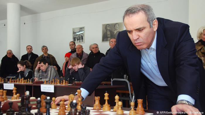 Der berühmte Schachspieler Garri Kasparov beugt sich über ein Schachspiel.